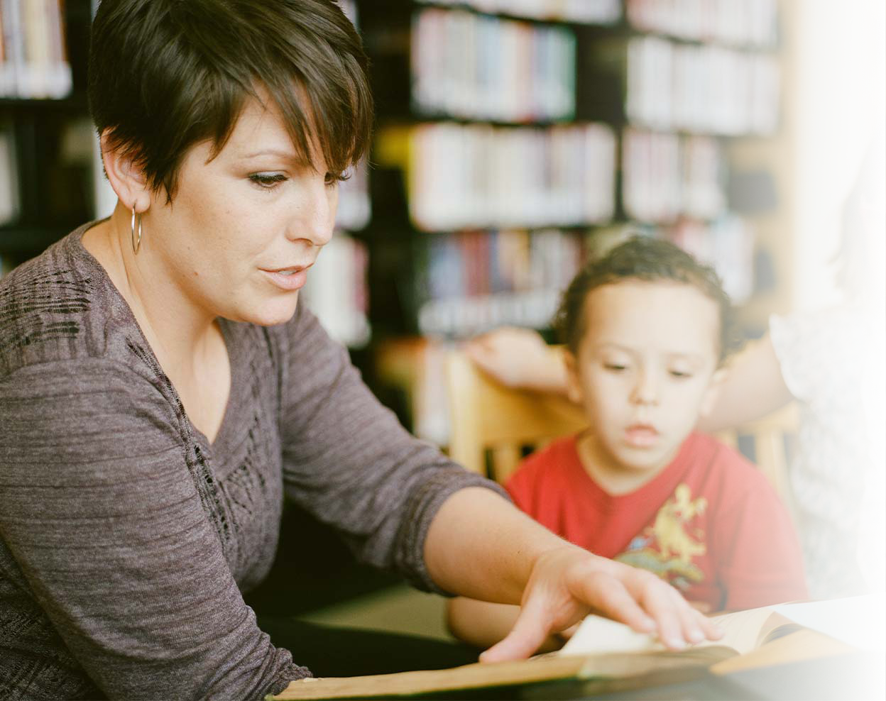 Educator reads with student in classroom